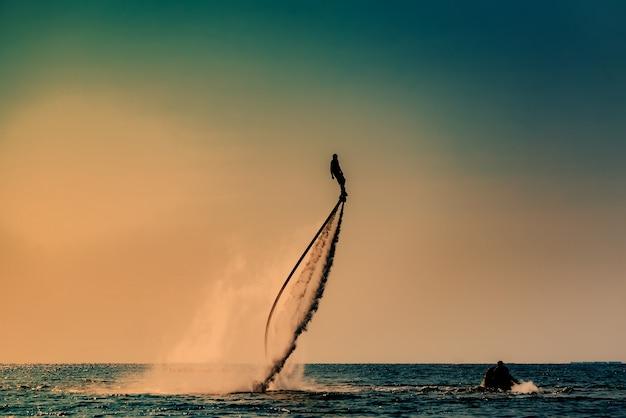 Imagen de la silueta de un hombre que muestra el fly board (aqua board) en el mar