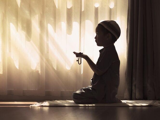 Imagen de silueta de niño musulmán en edad preescolar rezar a dios (haciendo dua o súplica). concepto de niño musulmán rezando.
