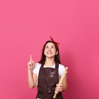 Imagen de sonriente mujer chef, cocinero o panadero con rodillo en las manos apuntando hacia arriba con su dedo índice y mirando hacia arriba