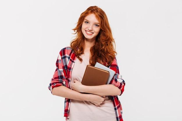 Imagen de sonriente mujer de jengibre en camisa abrazando libros