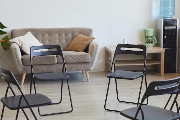 Imagen de superficie de sillas vacías en círculo listas para la sesión de terapia o la reunión del grupo de apoyo, espacio de copia
