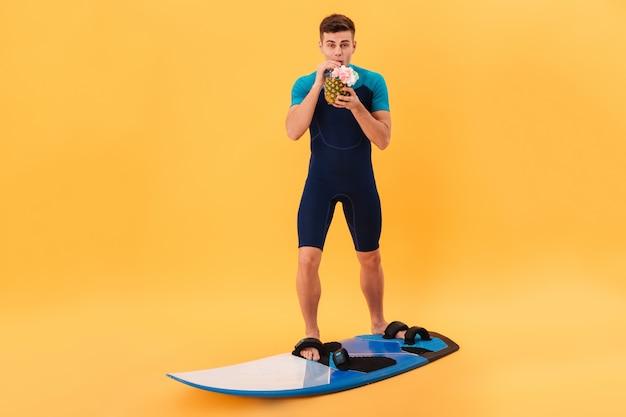 Imagen de surfer sonriente en traje de neopreno con tabla de surf mientras bebe un cóctel