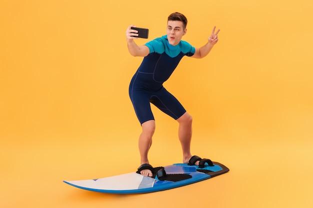 Imagen de surfista feliz en traje de neopreno usando una tabla de surf como en una ola mientras hace una selfie en un teléfono inteligente y muestra un gesto de paz