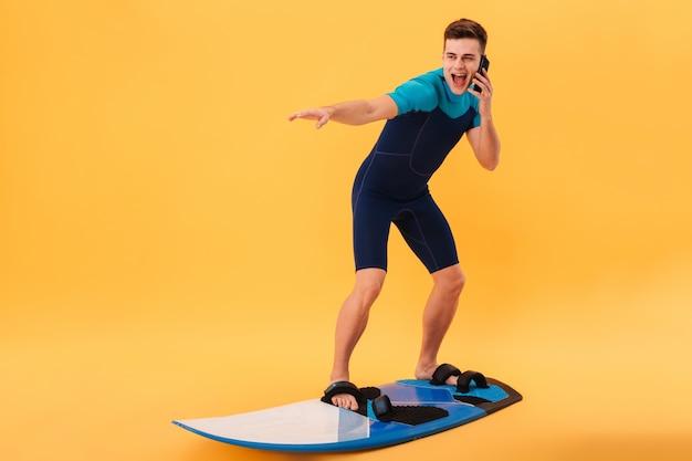 Imagen de surfista sonriente en traje de neopreno con tabla de surf mientras habla por teléfono inteligente