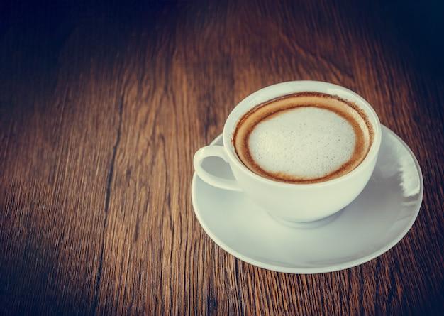 Imagen de una taza de café sobre fondo de mesa de madera con uso de espacio para mostrar textos