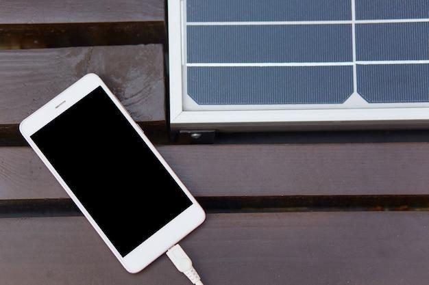 Imagen de un teléfono inteligente ligero acostado en un banco marrón, panel solar instalado en el interior, teléfono móvil apagado, pantalla negra
