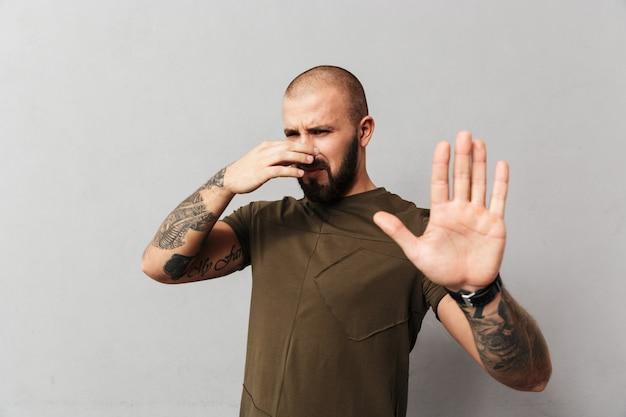 Imagen de un tipo musculoso con una camiseta informal cubriendo su nariz y mostrando un gesto de parada con la mano debido al mal olor, aislado sobre una pared gris