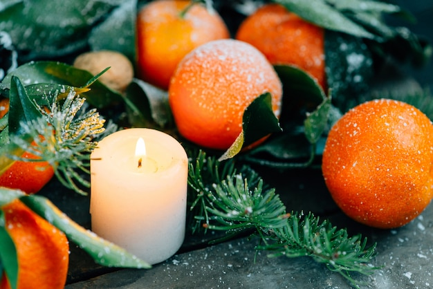 Imagen en tonos composición de navidad con mandarinas, piñas, nueces y velas sobre fondo de madera.