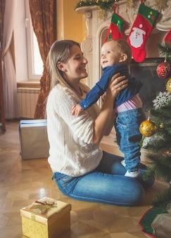 Imagen de tonos de feliz madre sonriente y su hijo de 1 año posando en el árbol de navidad