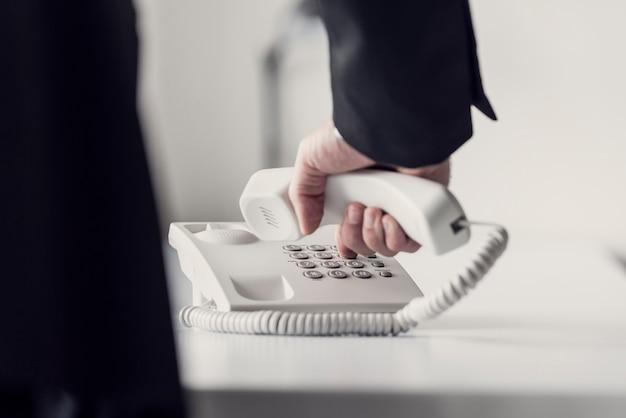 Imagen en tonos retro de un hombre de negocios que marca el número de teléfono en un teléfono fijo blanco clásico, vista de ángulo bajo entre el brazo y el cuerpo.