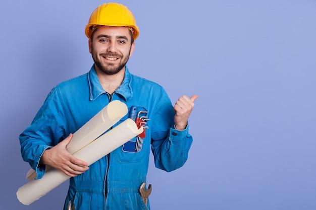 Imagen del trabajador guapo alegre barbudo enérgico de pie aislado sobre la pared azul en el estudio, manteniendo el puño, sosteniendo documentos de proyecto, obtener aprobación, tener éxito. copyspace para publicidad.