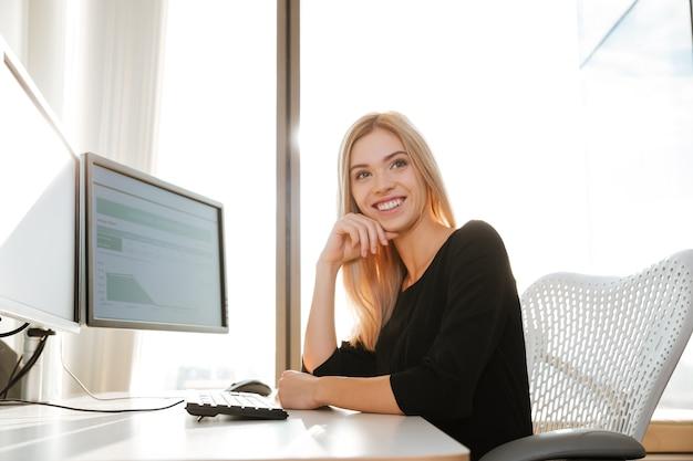 Imagen de trabajador joven feliz sentado en la oficina cerca de la computadora mientras mira a la cámara.