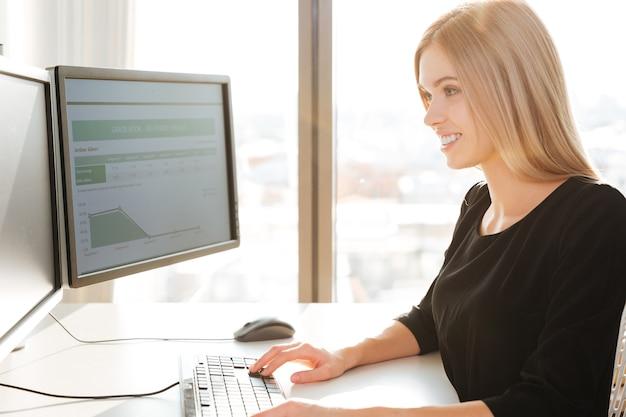 Imagen de trabajador joven feliz sentado en la oficina junto a la computadora. mirando la computadora.