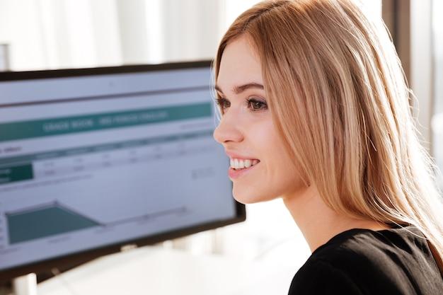 Imagen de trabajador joven feliz sentado en la oficina junto a la computadora. mirando a un lado.
