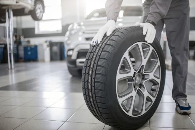 La imagen del trabajador se para y sostiene ambas manos sobre el neumático. el usa guantes. guy plantea. el coche se para detrás de él.