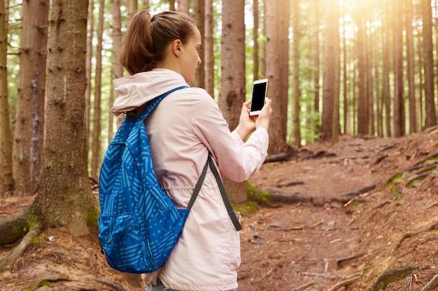 Imagen de turista activo y experimentado con chaqueta rosa y mochila azul, sosteniendo su teléfono inteligente, tratando de encontrar la conexión
