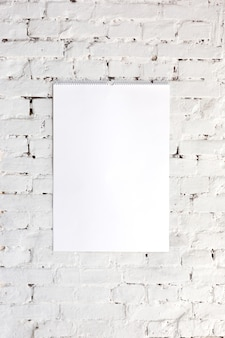 Imagen u hoja vacía en blanco en la pared de ladrillo blanco. copyspace, espacio negativo para tu publicidad.
