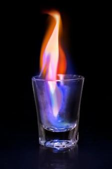 Imagen de vaso de chupito llameante, efecto estético de fuego ardiente.
