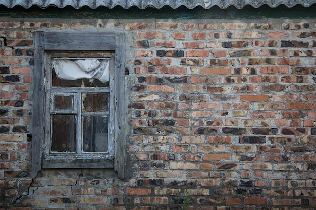 Imagen de la ventana vieja en la pared de ladrillo rojo
