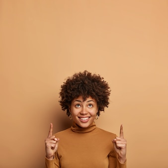 Imagen vertical de una atractiva mujer afroamericana con peinado rizado, llama su atención hacia algo hacia arriba, ayuda a tomar una mejor decisión de compra, vestida de manera informal, posa sobre una pared beige