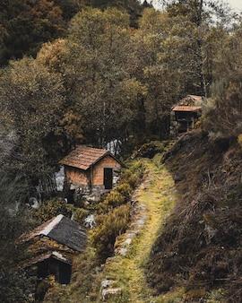 Imagen vertical de casas tradicionales en un pueblo al lado de una montaña rodeada de árboles