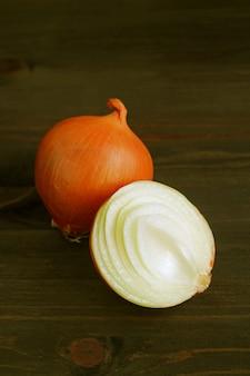 Imagen vertical de una cebolla entera y un corte por la mitad aislado en la mesa de madera marrón oscuro