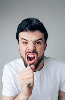 Imagen vertical de chico guapo con barba limpiando los dientes. usar cepillo de dientes con pasta de dientes. orán y cuidado dental. de cerca