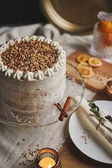 Imagen vertical de un delicioso pastel de navidad blanco con nueces y mandarina