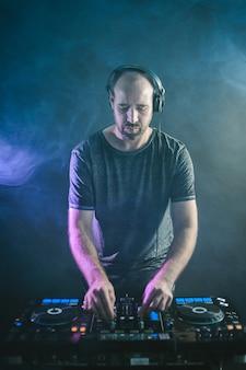 Imagen vertical de un dj masculino bajo las luces azules y el humo