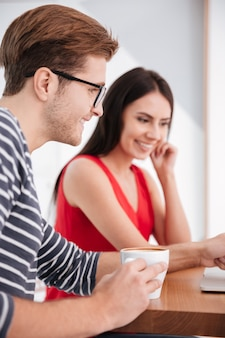 Imagen vertical de la feliz pareja sentada junto a la mesa con el portátil en la oficina. centrarse en el hombre