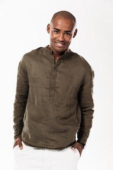 Imagen vertical del hombre africano sonriente con los brazos en los bolsillos y mirando