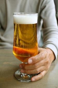 Imagen vertical de un hombre que sostiene un vaso de cerveza lager