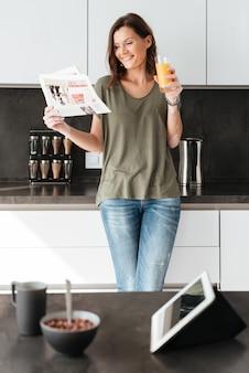 Imagen vertical de mujer casual sonriente leyendo el periódico y beber jugo en la cocina