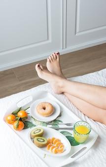 Imagen vertical de las piernas de una mujer encima de una cama con una colcha blanca junto a una bandeja de desayuno con rosquilla de mandarina, kiwi y jugo de naranja en la suave luz de la mañana