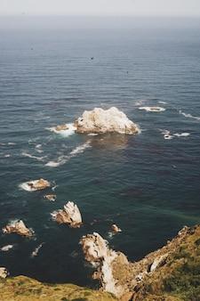 Imagen vertical de rocas en el océano cerca de la orilla de un acantilado