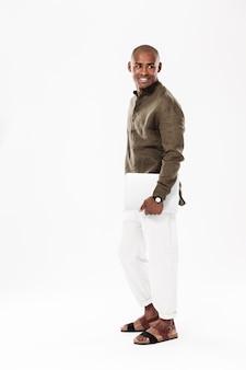Imagen de vista lateral de longitud completa del hombre africano sonriente con tablet pc y mirando hacia atrás