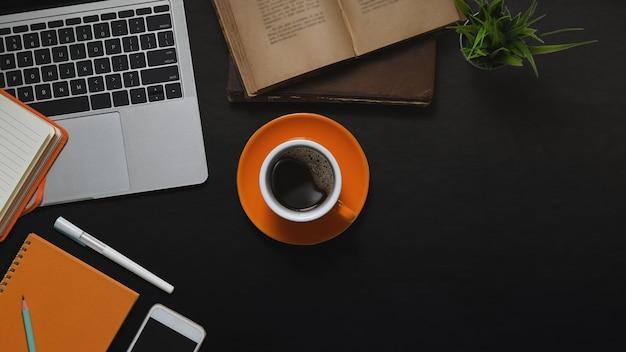 Imagen de la vista superior de la computadora portátil, la taza de café, los libros, la planta en maceta, el cuaderno, el diario, la pluma y el teléfono inteligente juntos en el escritorio de cuero negro. concepto de lugar de trabajo vintage.