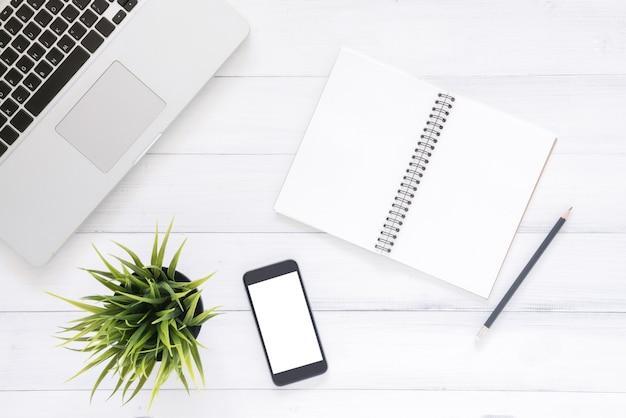 Imagen de la vista superior del cuaderno abierto con páginas en blanco y portátil en la mesa de madera