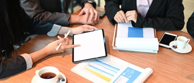 Imagen de la vista superior de empresarios que trabajan junto con una tableta de maqueta y un gráfico de finanzas