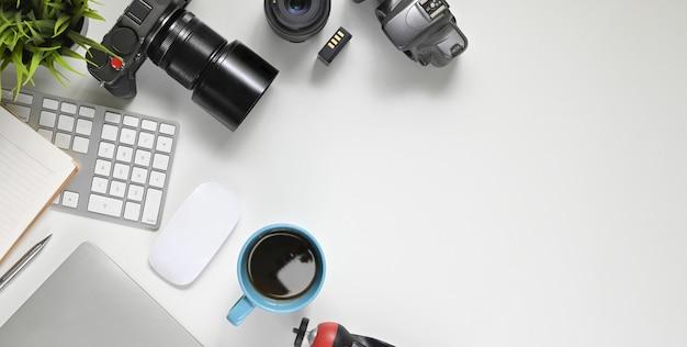 Imagen de la vista superior del escritorio de trabajo del fotógrafo con los accesorios que se ponen en él. cámara digital con lente, teclado inalámbrico, mouse, taza de café, nota, diario, bolígrafo, batería, lente, trípode y planta en maceta.