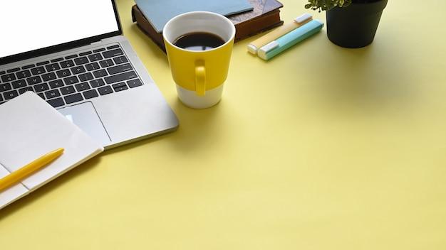 Imagen de la vista superior del lugar de trabajo colorido lleno de documentos, taza de café, cuaderno, bolígrafo, rotuladores y computadora portátil con pantalla vacía en blanco.