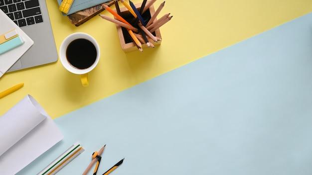 Imagen de la vista superior del lugar de trabajo de dos tonos que está lleno de documentos, brújula, taza de café, cuaderno, portalápices, rotuladores y computadora portátil con pantalla negra vacía.