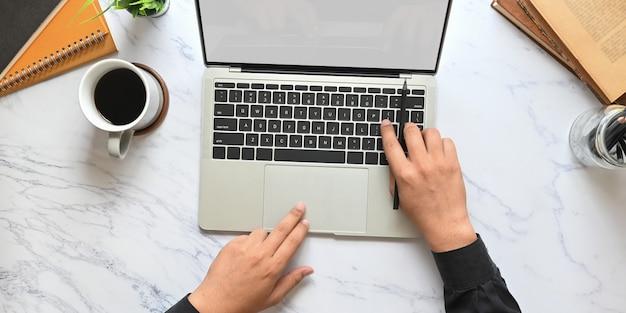 Imagen de la vista superior de las manos del hombre de negocios usando una tableta con pantalla blanca en blanco que pone en la mesa de textura de mármol con taza de café, cuaderno, libros, planta en maceta y portalápices.