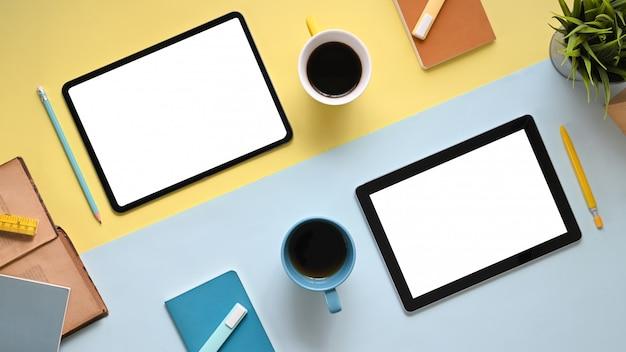 Imagen de la vista superior de la mesa de trabajo colorida con los accesorios que la ponen. flat pone dos tabletas con pantalla blanca en blanco, lápiz óptico, rotulador, cuaderno, diario, taza de café y planta en maceta.