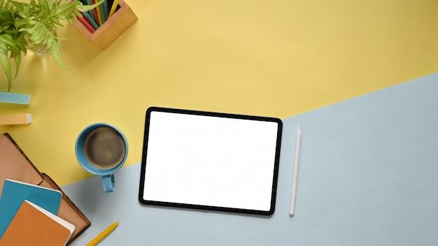 Imagen de la vista superior de la mesa de trabajo colorida con los accesorios que la ponen. tableta de computadora plana con pantalla blanca en blanco, lápiz óptico, rotulador, cuaderno, diario, taza de café y planta en maceta.