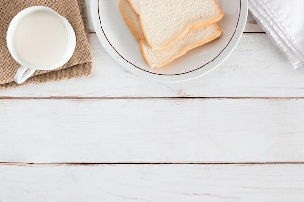 Imagen de la vista superior de pan de molde en un plato con leche caliente en una taza blanca sobre una mesa de madera blanca, desayuno en la mañana, hecho en casa fresco, espacio de copia