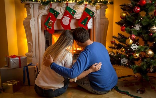 Imagen de vista trasera de la joven pareja relajándose junto a la chimenea en el salón