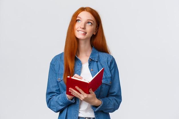 Imágenes creativas y atractivas de una adolescente, buscando inspiración como escribir un poema en su diario secreto, sosteniendo un bolígrafo y un cuaderno, sonriendo inspirado mirando hacia arriba, pensando