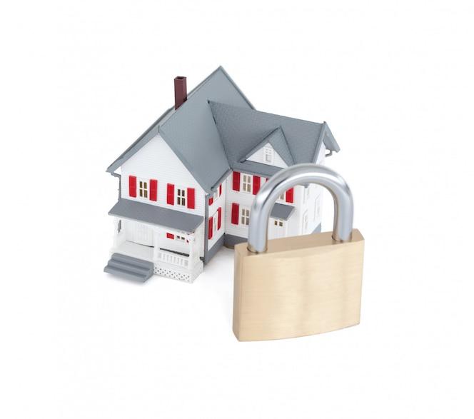 Imágenes de concepto de una casa gris en miniatura con un candado