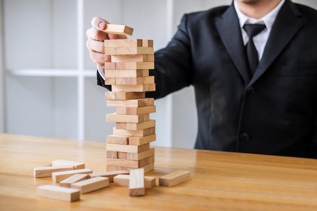 Imágenes de la mano de gente de negocios colocando y tirando bloques de madera en la torre.